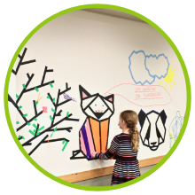 girl putting masking tape on whiteboard outlines of animals.