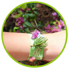 bracelet made of masking tape with leaves, pine needles and flowers stuck to it. Displayed on wrist.