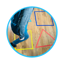 child jumping in large shapes made from masking tape on the floor