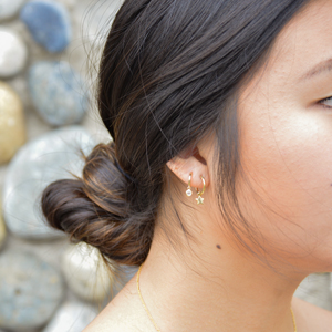 Model wearing CZ and Star Huggie Earrings