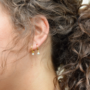 Model wearing CZ and Pearl Drop Huggie Earrings