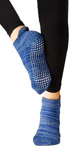 Model wearing black spandex tights and covered style yoga sock showing custom grip