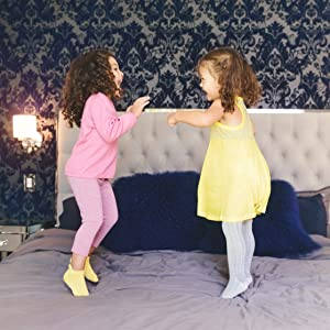 two girls in dresses jumping on bed in nonslip antiskid grip footie socks and legging tights