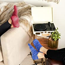 Two models in red and blue LA Active UK sticky gripper socks relaxing in house