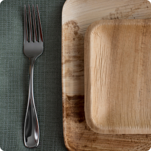 fork on napkin next to palm leaf dishes