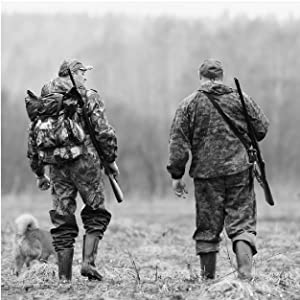 Black and white photo of 2 men in camo gear walking in a field with rifles slung on their backs.